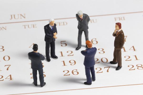カレンダーの上のビジネスマンたち